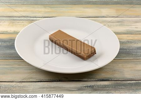 Two Layered And Flavored Nougat And Chocolate Hazelnut Nougat Candy Bar On White Plate