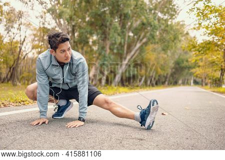 Young Man Stretching In The Park Before Running. Young Man Workout Before Fitness Training At The Pa