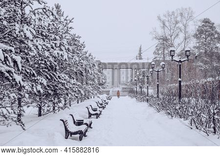 Snowfall In City Park, Blizzard And Cold Weather Concept. Trees, Benches, Lanterns Are Covered With