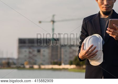 Asian Businessman Call Cellphone Hold White Hard Hat Looking On Screen, Man Worker Engineer