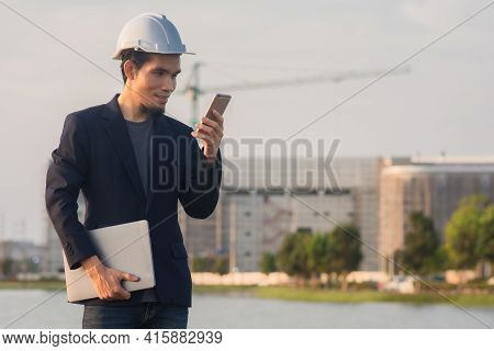 Businessman Using Mobile Phone Outdoor On Site Construction Background , Worker Hold Phone Happy Out
