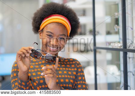 Smiling Pretty African Teen Gen Z Girl Holding New Sunglasses Frames In An Optician Store.