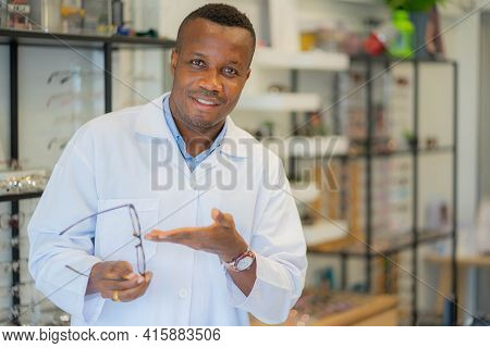 Portrait Of Optician Selling Glasses. Eye Doctor, Optometris At Work.