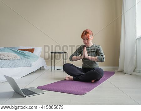 Woman Sitting Cross-legged On Yoga Mat And Meditating With His Arms Crossed Over His Chest. Online S