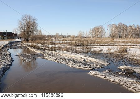 Flooded Dirt Road On The Outskirts Of The Village. The Field Road Is Flooded With Melted Snow From T
