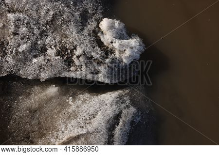 A Stream Of Meltwater Flows Into A Large Muddy Puddle. The Stream Between The Snow Makes Its Way To
