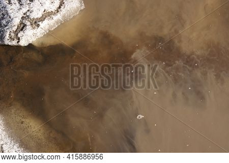Water From A Clean Stream Mixes With Muddy Muddy Water In A Puddle In Early Spring.