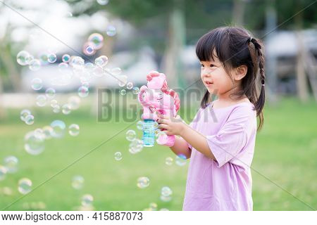 Child Play With The Bubble Gun And Have Fun. Happy Children Standing In The Grass. Sweet Smile Of A
