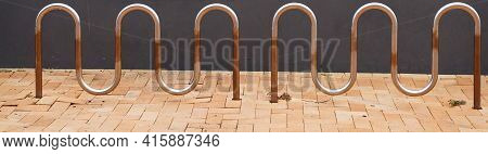 Metal Bicycle Parking Racks On Pavers Against A Grey Stone Wall In City Street
