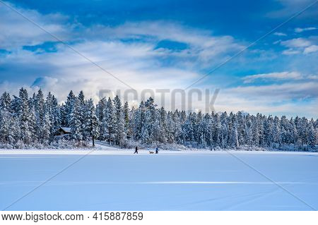 Cross Country Skiers With Dog On A Newly Frozen Lake Lillian Near Invermere, Bc, Canada