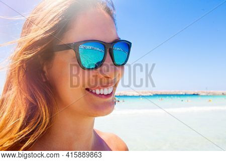 Summer Fun Vacation. Young And Beautiful Smiling Woman With Sunglasses. Blue Sea In The Background.
