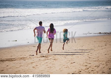 Happy Family Father, Mother And Baby Son Have Fun Together, Child Run By Water Pool Along Sea Surf O