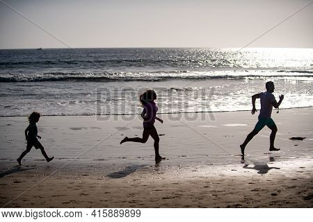 Happy Young Family Have Fun On Beach Run And Jump At Sunset. Active Parents And People Outdoor Activ
