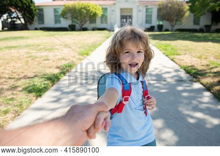 Pupil Holding Parent Fathers Hand On Blurred School Building Background. Child With Rucksacks Standi