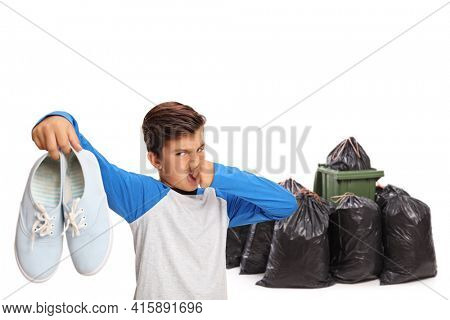 Chilf throwing a pair of smelly shoes in a waste bin isolated on white background