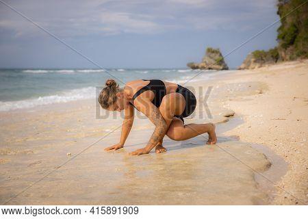 Yoga On The Beach. Young Caucasian Woman Practicing Yoga, Preparing For Bakasana, Crow Pose. Arm Bal