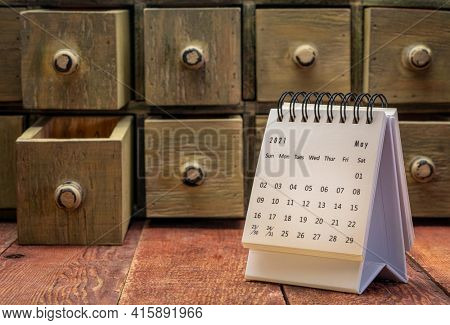 May 2021 - spiral desktop calendar on a weathered barn wood table with rustic apothecary drawers in background, time and business concept