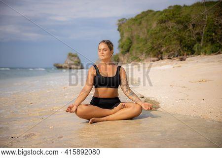 Lotus Pose. Beautiful Woman Sitting On The Sand In Padmasana. Hands In Gyan Mudra. Closed Eyes. Yoga