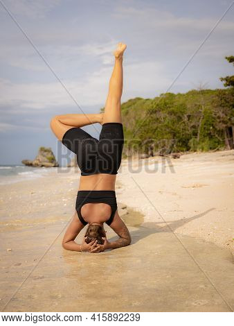Yoga Practice Near The Ocean. Caucasian Woman Practicing Salamba Shirshasana, Yoga Headstand Is An I