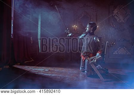 The noble knight in armor knelt down and raised his sword, looking at the light in the castle. Romance.