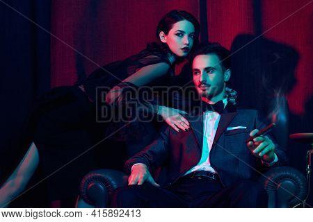 Glamorous lifestyle. Beautiful elegant couple in fashionable evening clothes posing in a luxury apartment. Fashion shot.