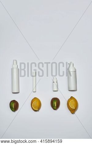 Flat Lay Of White Plastic Pump Bottles Or Containers Lying Vertically With Fresh Kiwi And Lemon Frui