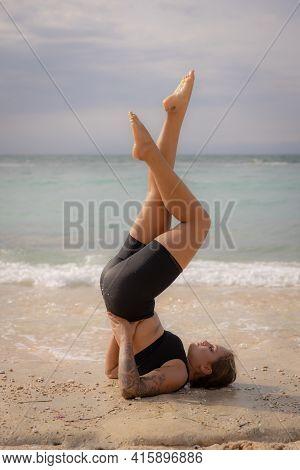 Yoga Practice Near The Ocean. Young Woman Practicing Salamba Sarvangasana, Shoulderstand. Inverted A