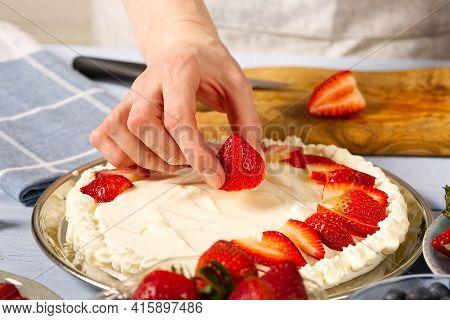 Woman Baker Stacks Strawberries On Meringue Strawberry Cake Base. Homemade Strawberries Cake Made Fr