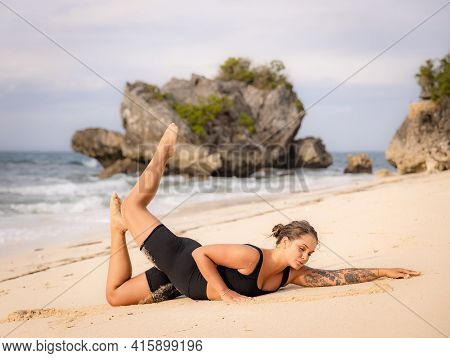 Yoga Bali. Caucasian Woman Practicing Salabhasana Variation B, Stag Locust Pose On The Beach. Outdoo