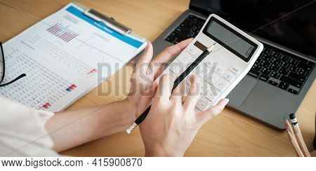 Close Up Of Woman Calculating Financial Or Taxes Or Household On Calculator, Female Calculate While