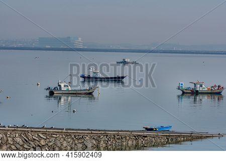 Small Fishing Boats Anchored In Harbor Near Boat Ramp On Hazy Overcast Morning.