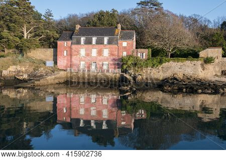 Sunny Day And Traditional Pink House On The Ile-aux-moines With Water Reflection In The Morbihan Gul