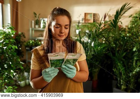 Girl Holding Plant Seeds While Standing In A Green Garden At Home. Home Garden Concept. Gardener Sel