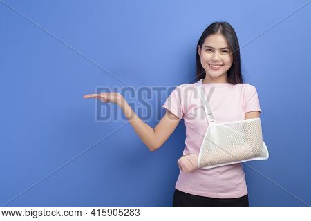 Portrait Of Young Woman With An Injured Arm In A Sling Over Blue Background In Studio, Insurance And