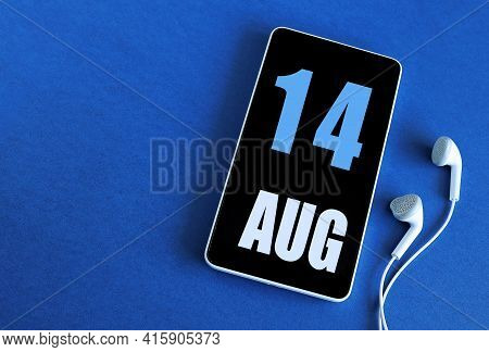 August 14. 14 St Day Of The Month, Calendar Date. Smartphone And White Headphones On A Blue Backgrou