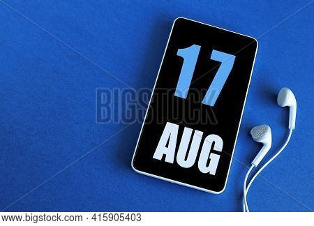 August 17. 17 St Day Of The Month, Calendar Date. Smartphone And White Headphones On A Blue Backgrou