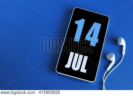 July 14. 14 St Day Of The Month, Calendar Date. Smartphone And White Headphones On A Blue Background