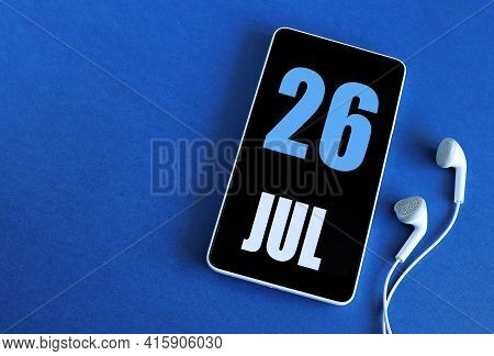 July 26. 26 St Day Of The Month, Calendar Date. Smartphone And White Headphones On A Blue Background
