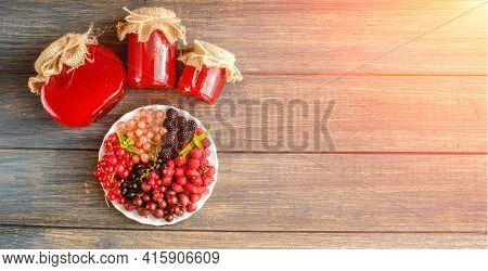 Assorted fresh summer berries and jam in jars. Raspberries, gooseberries, blackberries, currants, wild strawberries, strawberries.