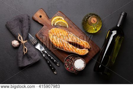 Grilled salmon steak and white wine. Fish steak with herbs and spices. Top view flat lay