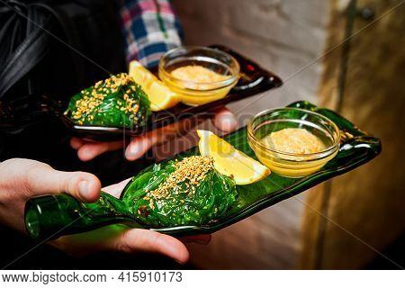 The Waiter Holds Plates With Chukka Seaweed Salad With Peanut Sauce, Lemon And Sesame Seeds. Close-u