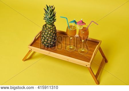 High Angle View Of Serving Wooden Tray With Food And Drink. Pineapple And Two Glasses With Exotic Su