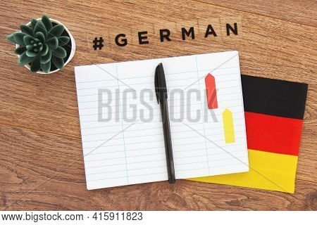 German Flag, Notebook, Pen And Inscription Hashtag German On A Wooden Desktop, Foreign Language Lear