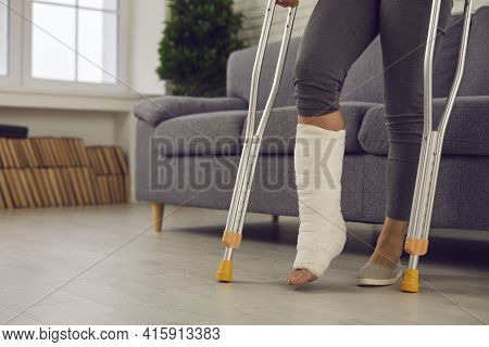 Woman Standing With Metal Medical Elbow Crutches And Showing Broken Injured Leg