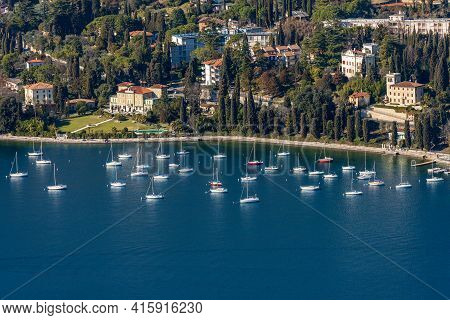 Aerial View Of The Harbor With Sailing Boats In Front Of Garda Town, Tourist Resort On The Coast Of