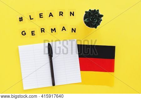 Yellow Background, Inscription With Hashtag Learn German, Notebook And Pen, Flag Of Germany, Foreign