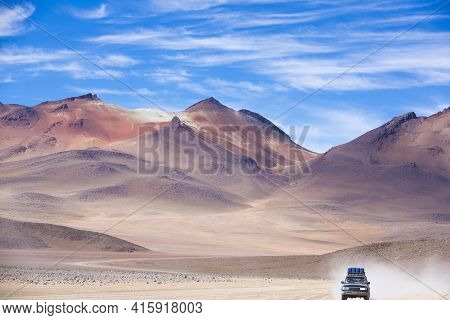 Off-road Vehicle Driving In The Atacama Desert, Bolivia With Majestic Colored Mountains And Blue Sky