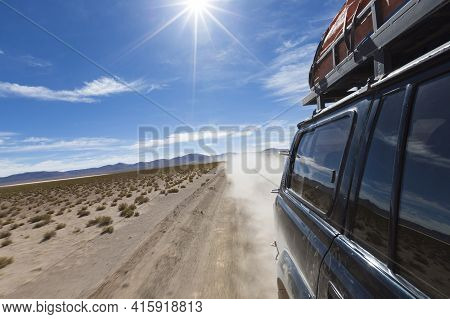 Off-road Vehicle Driving In The Atacama Desert, Bolivia With Mountains And Blue Sky In Eduardo Avaro