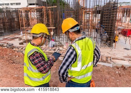 Construction Civil Engineer Technician And Architect With Hardhat On Construction Site Checking Sche