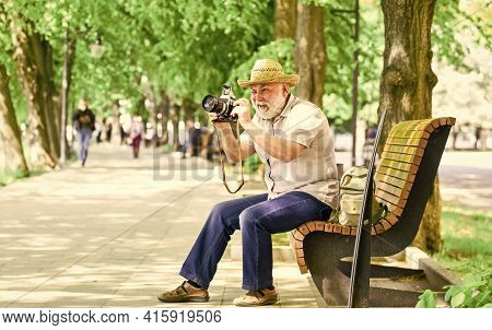 Tourist Concept. Travel And Tourism. Photographer Sit On Bench In Park. Capturing Spring Beauty. Enj